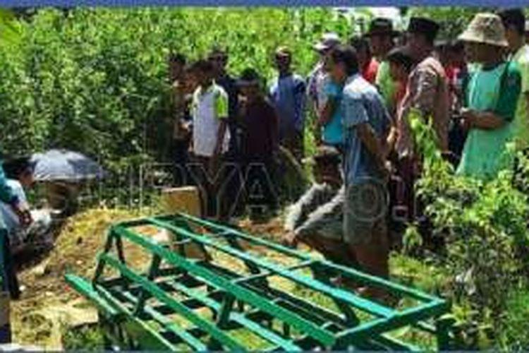 Warga Desa Karanglo memakamkan seorang warga yang meninggal, Jumat (1/4/2016).