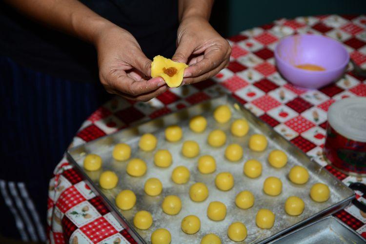 Ilustrasi proses membuat nastar. Selai nanas yang sudah dipulung dimasukkan ke adonan nastar.
