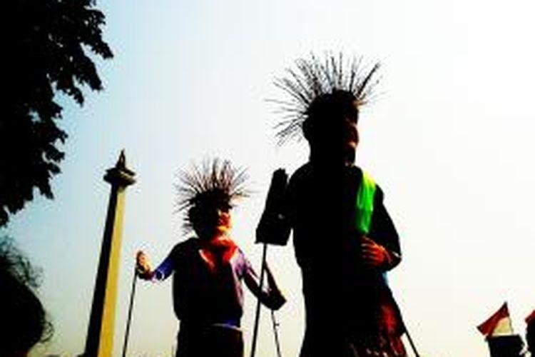 Sepasang ondel-ondel raksasa yang hadir di kawasan Tugu Monas, Jakarta, Minggu (18/8/2013) untuk memeriahkan Monas Jakarta Carnaval 2013