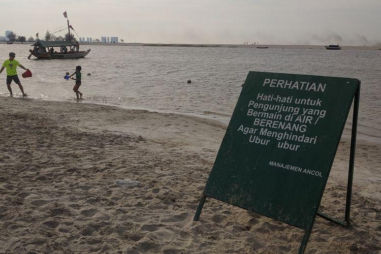 Imbauan agar warga menjauh dari ubur-ubur yang berenang ke pinggir Pantai Ancol Taman Impian, Pademangan, Jakarta Utara, Senin (7/10/2019)
