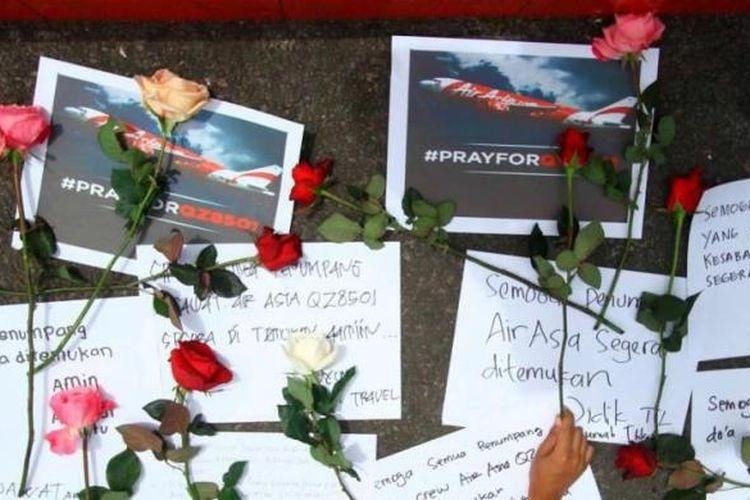 Anggota Batu Profesional Tourism Association (Bapta) dan wisatawan melakukan doa bersama untuk penumpang AirAsia QZ8501 di Alun-alun Kota Batu, Jatim, Selasa (30/12/2014). Pesawat AirAsia QZ8501 mengangkut 155 penumpang serta 7 kru, jatuh pada Minggu pagi, saat penerbangan dari Surabaya ke Singapura.