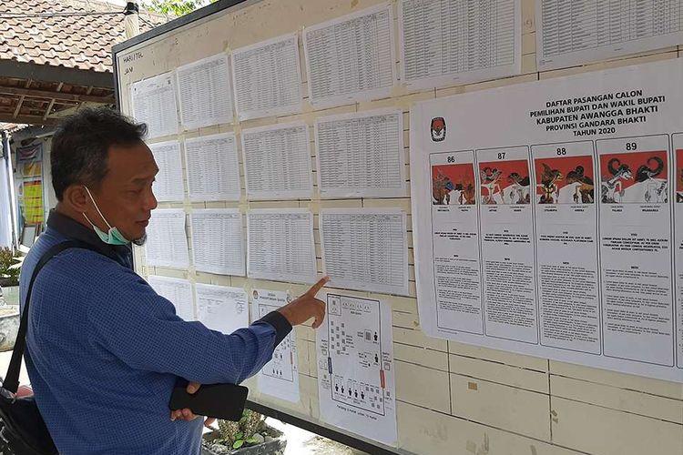 Warga mengecek daftar nama sebelum memasuki TPS pada simulasi Pilkada 2020 di Balai Kelurahan Piyaman, Kecamatan Wonosari, Kabupaten Gunungkidul, Yogyakarta, Sabtu (21/11/2020). Komisi Pemilihan Umum (KPU) Kabupaten Gunungkidul menggelar simulasi Pilkada yang dijadwalkan dihelat pada 9 Desember 2020, dengan protokol kesehatan tata cara pencoblosan yang ketat untuk mencegah penyebaran Covid-19.