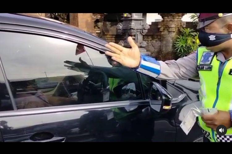 Tangkapan layar video viral pengemudi mobil di Bali yang mengumpat petugas kepolisian usai dihentikan karena melanggar lampu merah.