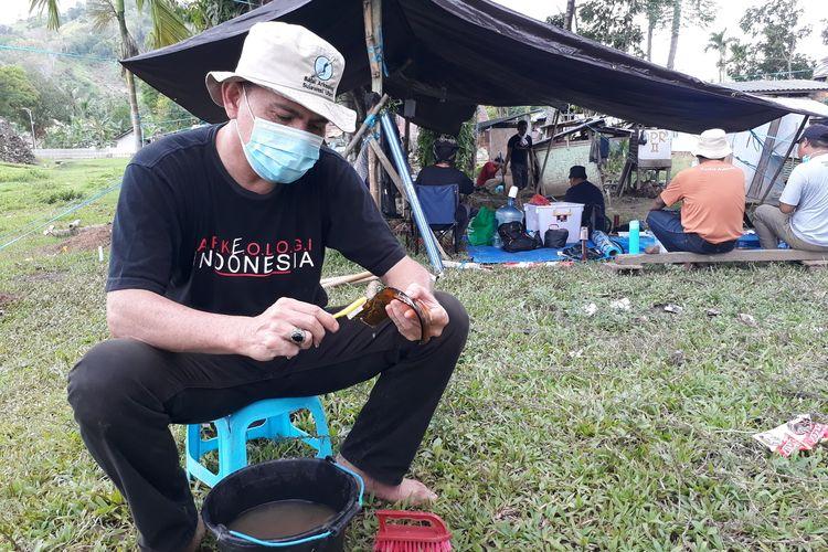 Handry Karisoh salah seorang anggota tim peneliti Balai Arkeologi Sulawesi Utara tengah membersihkan pecahan botol yang ditemukan pada Sabtu (26/6/2021) di reruntuhan Benteng Kota Mas. Banyak temuan pecahan keramik di kawasan ini yang menunjukkan periode waktu yang berbeda.