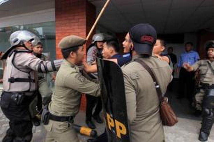 Aparat kepolisian dan Satpol PP bentrokan dengan warga Kampung Pulo, Jakarta Timur, Kamis (20/8/2015). Kerusuhan terjadi karena warga menolak digusur dan dipindahkan untuk normalisasi Kali Ciliwung.