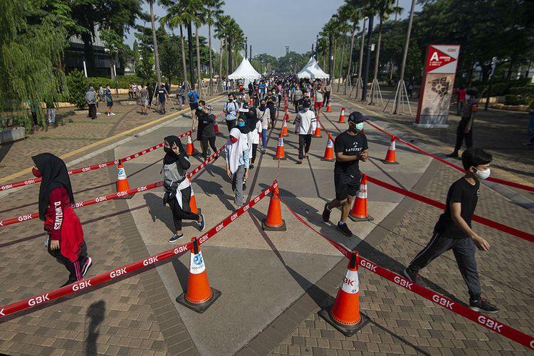 Sejumlah warga mengantre untuk memasuki area ring road Stadion Utama Gelora Bung Karno (SUGBK) di Senayan, Jakarta, Minggu (21/6/2020). Selain membatasi akses menjadi dua pintu masuk dan satu pintu keluar, pengelola SUGBK juga melakukan pembatasan dengan membagi ke dalam sejumlah sesi di akhir pekan dengan durasi setiap sesi selama satu jam dan jumlah maksimal 1.000 pengunjung di dalam area ring road untuk meminimalisir potensi penyebaran COVID-19.