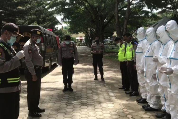 Tim dari Dokkes RS Bhayangkara berpakaian APD berdoa sebelum melakukan pemakaman terhadap pasien positif covid-19 yang meninggal