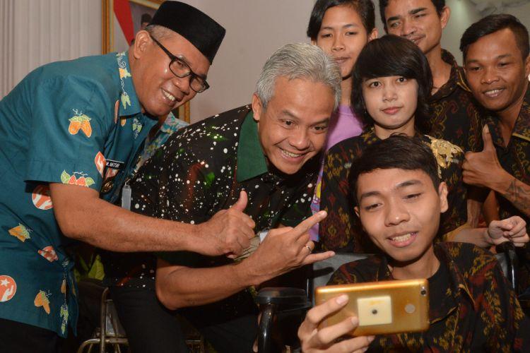 Gubernur Jawa Tengah Ganjar Pranowo sedang berselfie bersama anak-anak muda