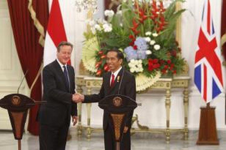 Presiden Joko Widodo (kanan) dan  Perdana Menteri Inggris David Cameron bersalaman usai memberikan keterangan pers usai pertemuan bilateral di Istana Merdeka, Senin (27/7/2015) petang. Kunjungan kali ini difokuskan Cameron untuk meningkatkan kerja sama Inggris dengan negara-negara Asia Tenggara