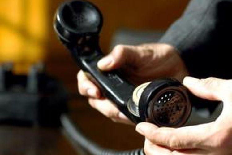 Ilustrasi memasang alat penyadap di dalam sebuah telepon.