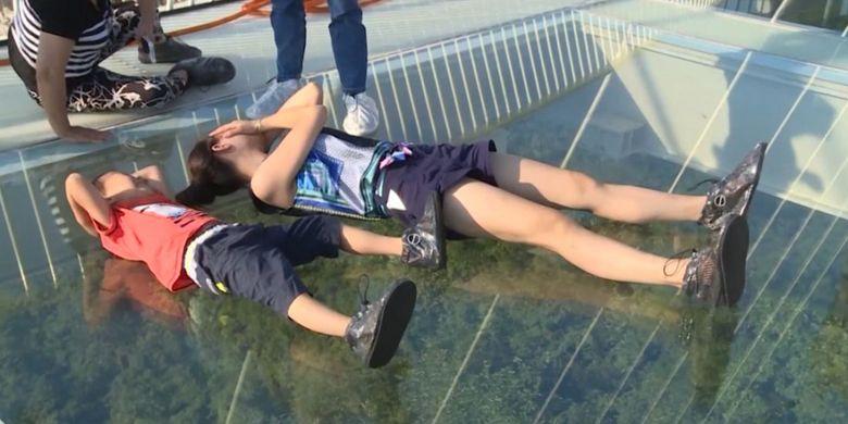 Pengunjung tampak ngeri saat berada di jembatan kaca gantung Hongayu di China.