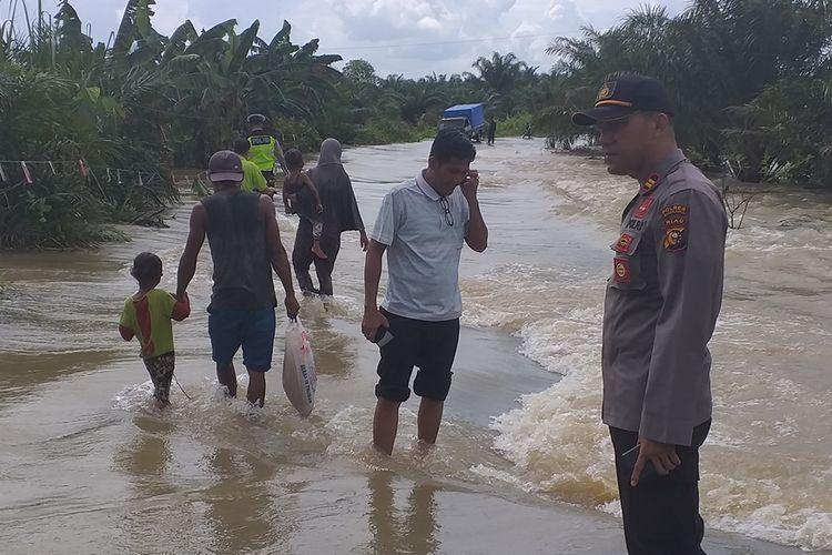 Kapolsek Bonai Darussalam Iptu Riza Effyandi dan anggotanya mengatur lalu lintas dan membantu menyeberangkan warga yang melewati jalan yang digenangi banjir di Desa Sontang, Kecamatan Bonai Darussalam, Kabupaten Rohul, Riau, Sabtu (30/11/2019).