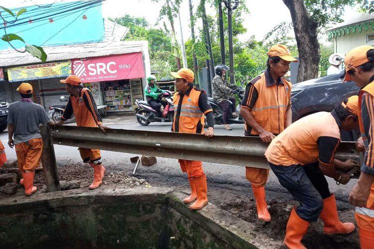 Petugas PPSU Kelurahan Setu saat memasang guard rail di Jalan Raya Pagelarang, Setu, Jakarta Timur, Jumat (31/1/2020).