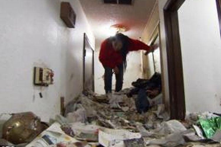 Michelle (56) sampai harus menunduk saat berjalan di dalam rumahnya akibat tumpukan sampah yang hampir mencapai langit-langit kediamannya. Kegemaran menimbun banyak barang membuat kediaman perempuan ini dipenuhi sampah setinggi pinggang orang dewasa.
