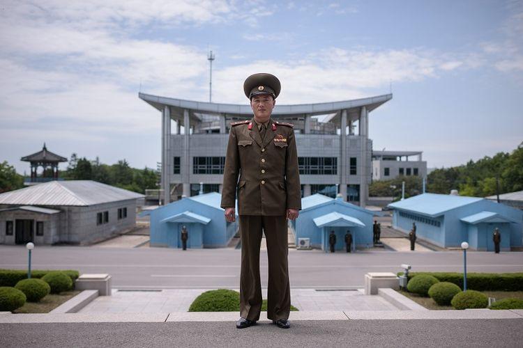 Dalam foto ini terlihat seorang prajurit Korea Utara berpose di Zona Demiliterisasi yang memisahkan kedua Korea. Di belakangnya terlihat Rumah Perdamaian lokasi KTT Korea yang akan digelar pada Jumat (27/4/2018).