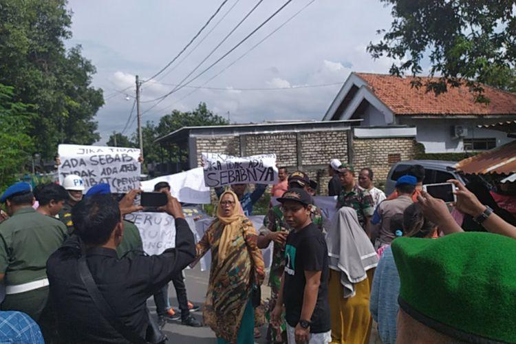 Anggota keluarga Serda Ali Sahbana, pelaku pembacokan anggota Polres Pamekasan berunjuk rasa di sela-sela proses rekonstruksi yang dilakukan oleh Polisi Militer, Selasa (7/1/2020).