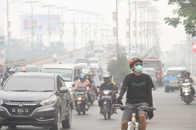 Warga bersepeda menggunakan masker pelindung pernapasan ketika melintas di Jalan Ahmad Yani yang terpapar kabut asap di Banjarmasin, Kalimantan Selatan, Minggu (15/9/2019). Kebakaran hutan dan lahan (Karhutla) di sejumlah wilayah Provinsi Kalsel mengakibatkan Kota Banjarmasin terpapar kabut asap dengan aroma yang menyengat dan bertambah pekat dalam beberapa hari terakhir.