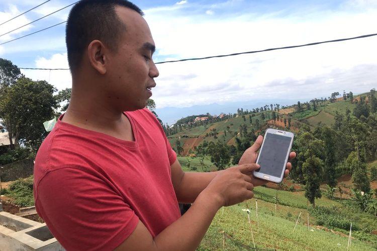 Ujang Margana (25), petani asal Cimenyan, Kabupaten Bandung, mempraktekkan penyiraman kebun lewat aplikasi di gawainya.