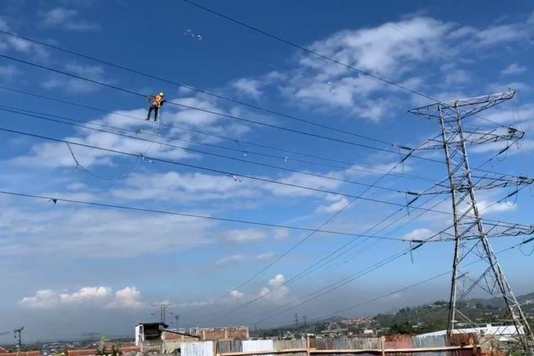 Petugas PLN sedang membersihkan benang layang-layang yang terlilit di kabel listrik jaringan SUTT maupun SUTET, Bandung, Jawa Barat.