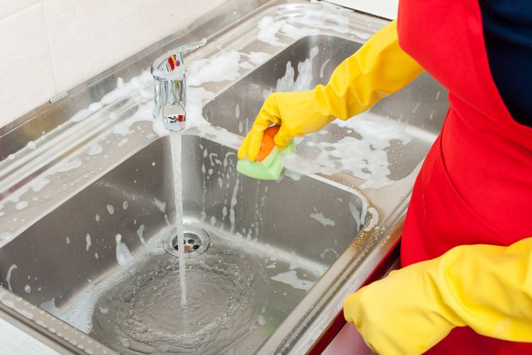 Ilustrasi orang sedang menggosok tempat cuci piring.