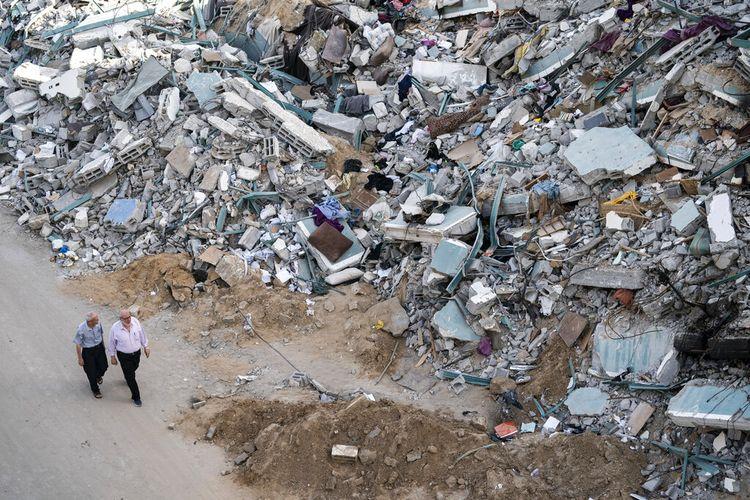 Orang-orang berjalan di dekat puing-puing gedung al-Jalaa menyusul gencatan senjata yang dicapai setelah perang 11 hari antara penguasa Hamas Gaza dan Israel, di Kota Gaza, Jumat, 21 Mei 2021.