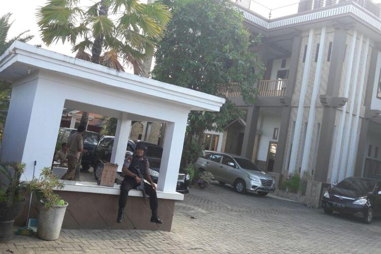 Petugas kepolisian bersenjata lengkap mengawal tim KPK yang melakukan pengeledahan di rumah pribadi mantan bupati Konawe Utara, Aswad Sulaiman. (KOMPAS.COM/KIKI ANDI PATI)