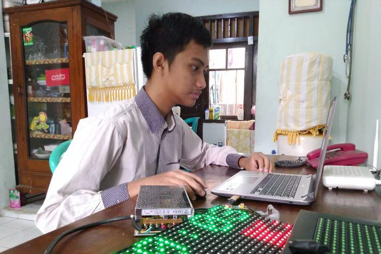 Hanif Arroisi Mukhlis saat sedang membuat bahasa pemrograman untuk jam digital karyanya bersama sang ayah.