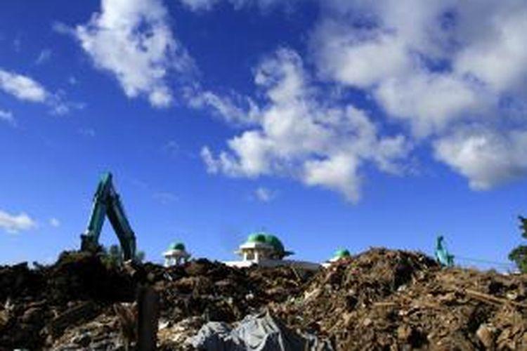 Tumpukan sampah banjir bandang yang dibuang di tengah pemukiman warga sampai menutupi pemandangan ke arah Masjid Nurul Huda, Ketang Baru, Manado.