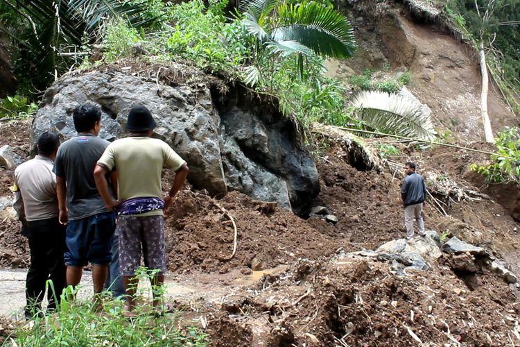 Material longsor berupa batu besar menutup badan jalan penghubung dari arah Toraja Utara, Sulawesi Selatan menuju Mamuju, Sulawesi Barat, di Lembang Sikuku, Jumat (21/02/2020)