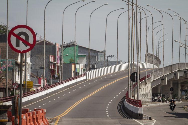 Pengendara melintas di samping jembatan Flyover Palur yang ditutup di Karanganyar, Jawa Tengah, Rabu (14/7/2021). Polres Karanganyar menutup total jalan layang atau flyover yang menghubungkan Kota Solo dengan Kabupaten Karanganyar tersebut untuk mengurangi mobilitas warga selama Pemberlakukan Pembatasan Kegiatan Masyarakat (PPKM) Darurat. ANTARA FOTO/Mohammad Ayudha/foc.