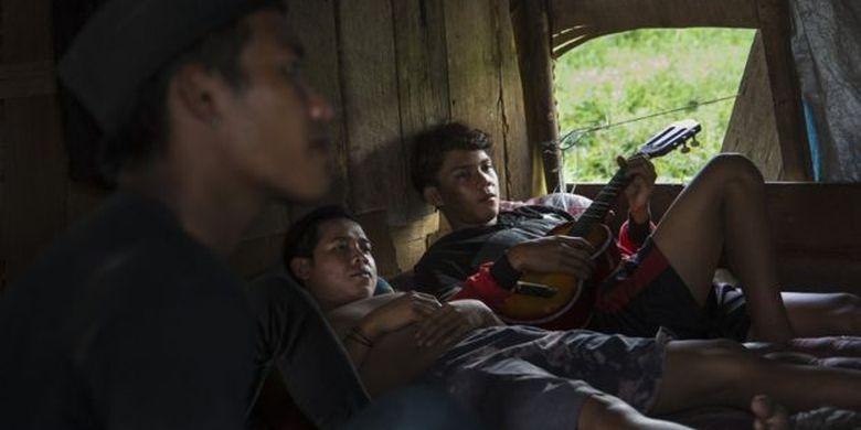 Tiga pekerja pertambangan di Samarinda beristirahat di gubuk berbahan kayu. Sebagian besar pemerintah daerah di Kaltim menggantungkan pemasukan dari industri batu bara.