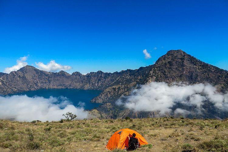 Seorang pendaki dan tendanya dengan latar belakang Segara Anak di Gunung Rinjani.