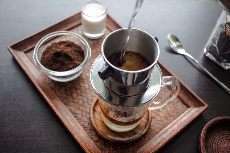 Ilustrasi kopi Vietnam drip terbuat dari bubuk kopi Vietnam menggunakan alat Vietnam drip.