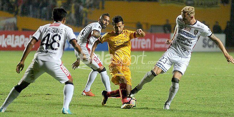 Pemain Sriwijaya FC, Manucher Dzalilov (tengah), berusaha melewati hadangan pemain Bali United pada laga leg pertama semifinal piala Presiden di Stadion Gelora Sriwijaya Jakabaring Palembang, Minggu (11/2/2018).