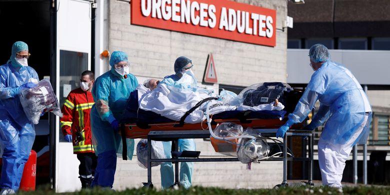 Seorang pasien yang terinfeksi virus corona dibawa dengan brankar oleh petugas medis Perancis sebelum diterbangkan menggunakan helikopter dari rumah sakit Strasbourg ke Pforzheim, Jerman, pada 24 Maret 2020.