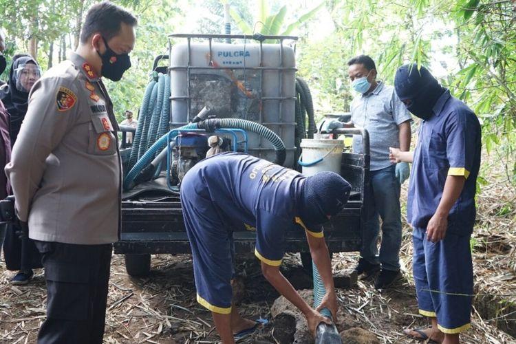 Kapolres Sukoharjo AKBP Wahyu Nugroho S menyaksikan proses pembuangan limbah ciu yang diperagakan tersangka dalam konferensi pers di Sukoharjo, Jawa Tengah, Jumat (17/9/2021).