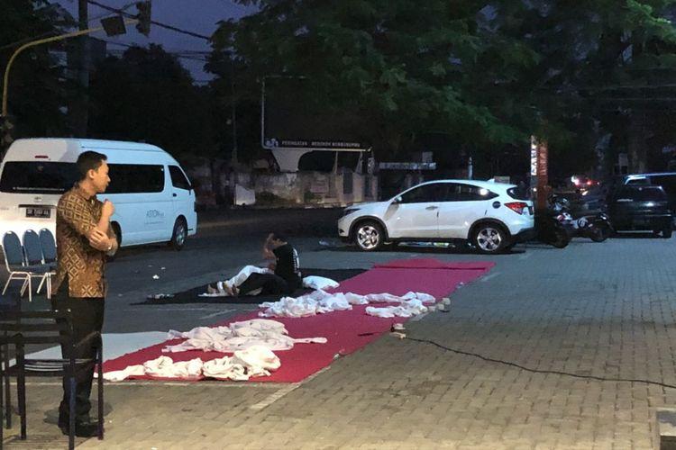 Para tamu hotel tidur di area parkir Hotel Aston Inn Mataram setelah gempa magnitudo 7 terjadi di Lombok, Minggu (19/8/2018).