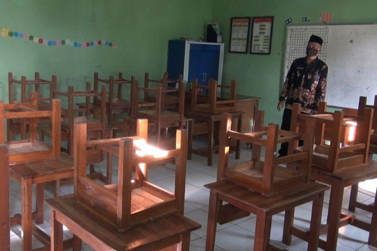 Seorang guru MI Bina Amanah Sidapurna, Kabupaten Tegal, usai menata kursi yang dinaikkan ke atas meja setelah sekolah menghentikan sementara KBM tatap muka menyusul puluhan pedagang pasar sekitar sekolah terkonfirmasi positif Covid-19, Jumat (20/11/2020)