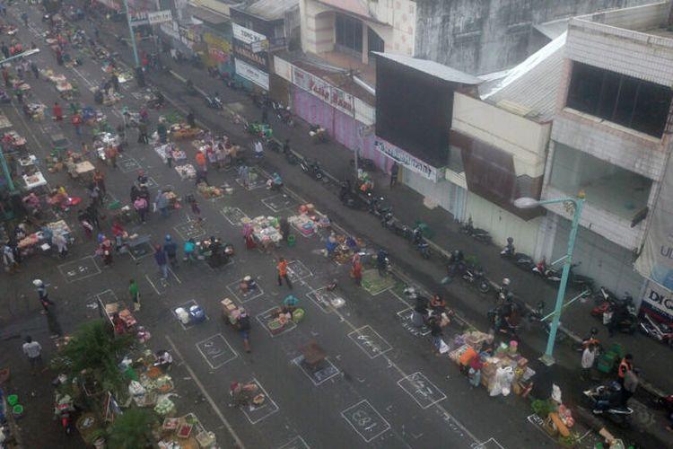 Pedagang  berjualan di Jalan Jenderal Sudirman, Kota Salatiga, Jawa Tengah, pada hari pertama  penataan Pasar Pagi Salatiga, Senin (27/4/2020). Penataan dengan penerapan jarak satu meter antar pedagang tersebut berlangsung mulai pukul 01.00 hingga pukul 06.30. Sebanyak 853 pedagang pasar itu mengikuti upaya penataan yang dilakukan untuk mencegah penyebaran pandemi Covid-19 tersebut.