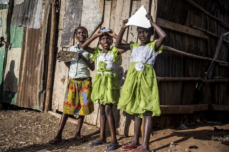 Anak-anak perempuan di Kenya bermain dengan pecahan cermin di kawasan kumuh di Nairobi.