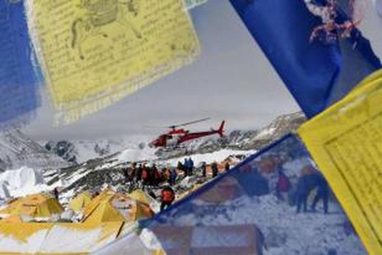 Bendera doa dengan latar belakang tim SAR menggunakan helikopter membawa korban gempa di dari Everest Base Camp, 26 April 2015, sehari setelah gempa berkekuatan 7.9 SR mengguncang Nepal.