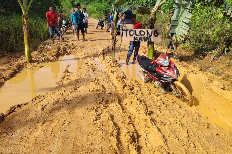 Warga Desa Mata Air menanam pisang di jalan rusak yang menghubungkan Desa Mata Air dan Desa Bukit Permata, Rabu (15/1/2020).