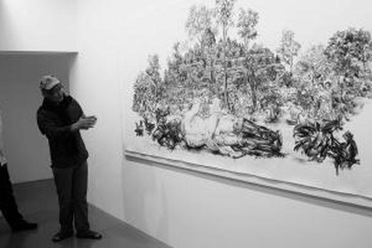 "Seniman Singapura, Jimmy Ong (kanan), menjelaskan lukisannya yang berjudul ""Mapping Boro Budur"" kepada pengunjung di Galeri Fost, kompleks Barak Gillman, Singapura, Selasa (20/1/2015). Karya Jimmy sebagai reimaji dari suasana seperti yang dituturkan dalam buku History of Java karya Thomas Stamford Raffles terbitan tahun 1817."
