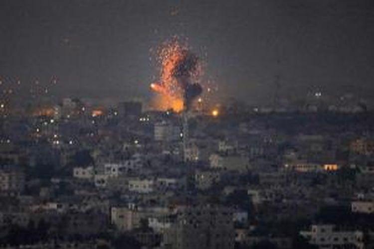 Api terlihat sesaat setelah sebuah roket yang dilancarkan militer Israel menghantam sebuah gedung di kota Gaza, 9 Juli 2014. Setidaknya 24 warga Palestina tewas dalam serangan tersebut.