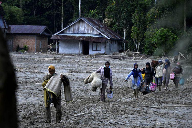 Warga mengangkat barang miliknya melewati material lumpur di Desa Radda, Kabupaten Luwu Utara, Sulawesi Selatan, Sabtu (18/7/2020). Pascabanjir bandang sejumlah warga yang terdampak mulai mengambil barangnya yang masih bisa digunakan.