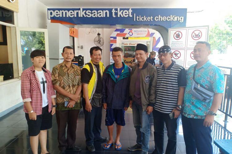 Agus Bustanul Arifin (45) (tengah), warga Garut, Jawa Barat yang ditemukan di Kota Madiun setelah hilang 20 tahun dari kampung halamannya dipulangkan melalui Stasiun Madiun.