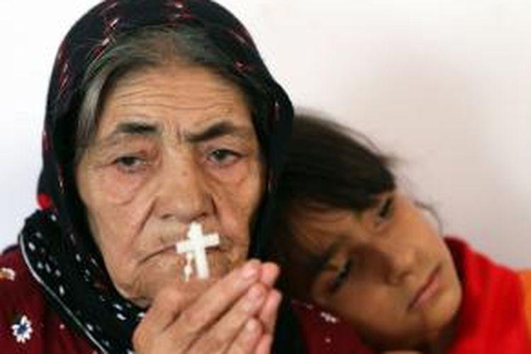 Seorang perempuan tua warga kota Qara Qosh bersama cucunya, kini mengungsi di kota Arbil setelah kotanya dihujani tembakan mortir selama beberapa hari terakhir ini.