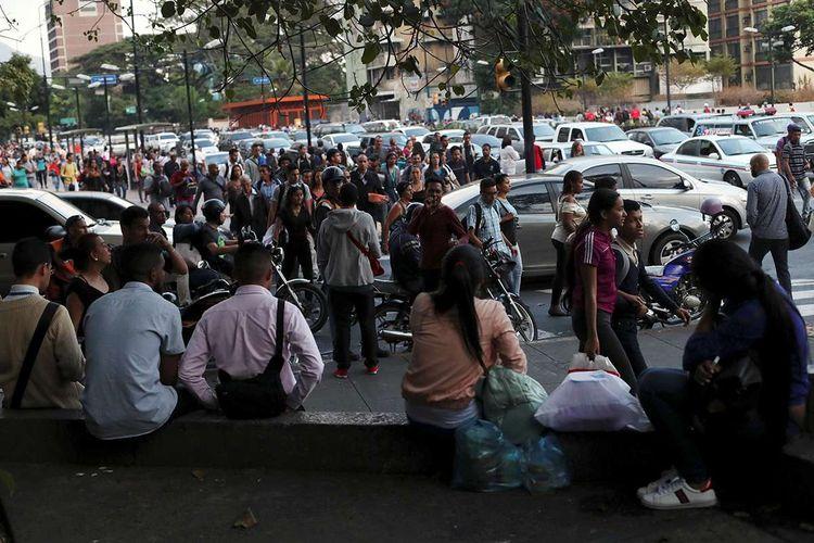 Warga berjalan di sepanjang jalan saat terjadi listrik padam di Karakas, Venezuela, Kamis (7/3/2019). Di tengah krisis yang melanda Venezuela, pemadaman listrik massal yang terjadi berhari-hari di sejumlah kawasan negara itu menimbulkan banyak kekacauan seperti penjarahan hingga kesulitan air.