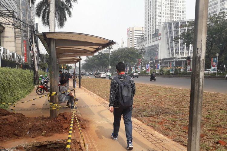 Halte bus di depan Gedung Graha CIMB Niaga, Jalan Jenderal Sudirman, yang aksesnya terhalang area rerumputan, Selasa (24/7/2018).
