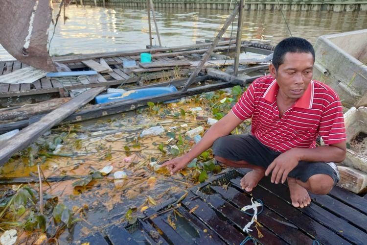 Nelayan bernama Ambo Dale saat menunjuk sisa-sisa tumpahan minyak kelapa sawit di areal tambak ikan miliknya di Gang Nelayan, Kelurahan Rawa Makmur, Kecamatan Palaran, Kota Samarinda, Kaltim, Kamis (15/4/2021).